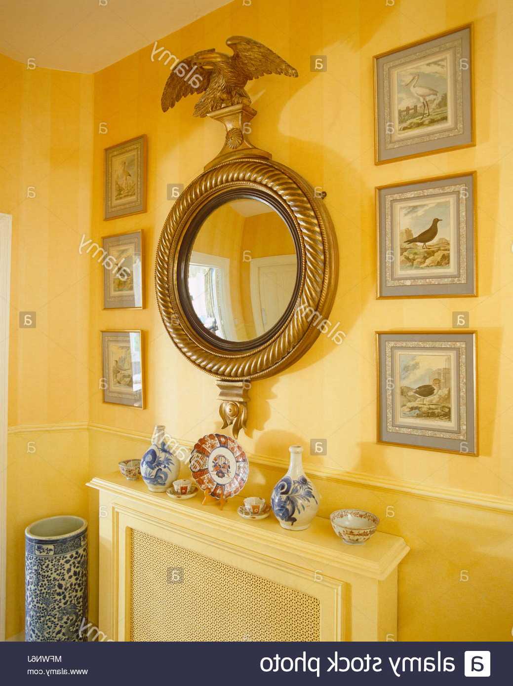 Well Liked Yellow Wall Mirrors With Regard To Ornate Round Gilt Mirror Above Radiator Cover On Yellow Wall Stock (View 16 of 20)